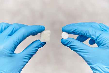 Hands in rubber gloves hold sugar and a tablet