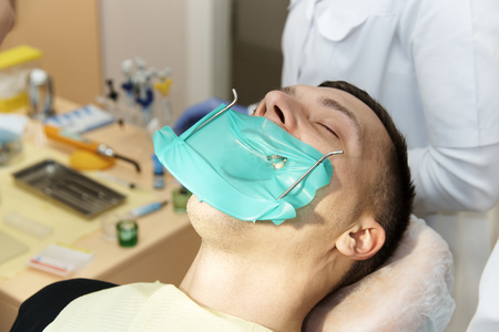 The young man in the dental chair heals the tooth with the use of a system of rubber dams with latex scarves and metal clips, the production of photopolymer composite fillings.