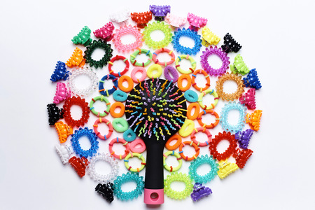 Bright multicolored comb in a circle of small colorful hairpins and rubber bands for hair on a white background.