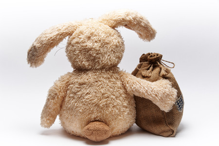 Soft toy rabbit sits with his back with a bag on a white background. Stock Photo