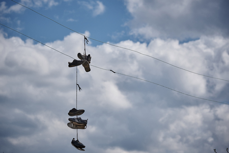 Torn old sneakers hang on the wire against the sky.