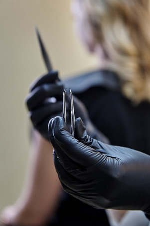 Hand stylist in black gloves with metal tweezers close-up. Stock Photo