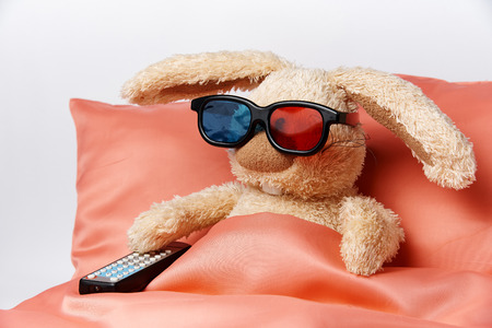 A toy rabbit in stereo glasses with a remote control from the TV lie in bed. Stock Photo