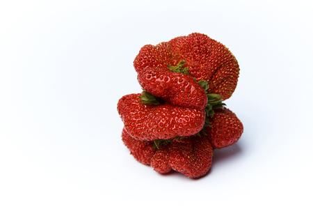Ripe juicy strawberry of strange unusual shape on a white background.