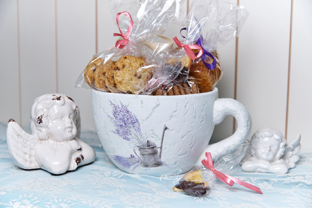 Decorative big beautiful cup with biscuits in gift package. Stock Photo