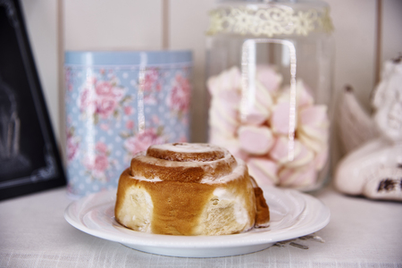 Sweet bun with glaze on a white plate near the jar with a marshmallow and biscuit. Stock Photo