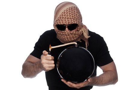 A man hidden under the arafatka and black glasses ignites a bomb on a white background. The concept of terrorism.