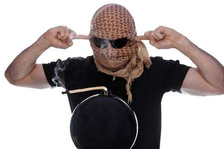 The man hidden under the arafatka and black glasses closes his ears with his hands and a lighted bomb with smoke on a white background. The concept of terrorism. Stock Photo