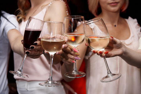 Ð¡linking glasses of cold wine in female hands. 写真素材