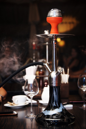 Hookah in a cloud of smoke on a table in a nightclub. Stock Photo