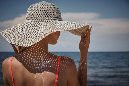Girl in hat with sunscreen in the shape of the sun on her back.