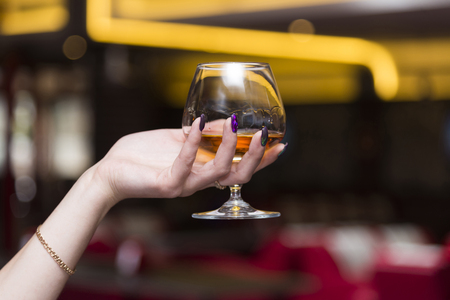 Female hand holding a glass of cognac, blurred background