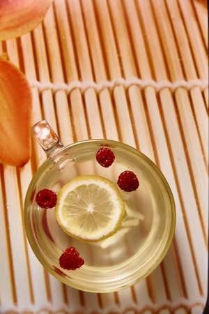 Glass cup with hot ginger tea with lemon and raspberries.