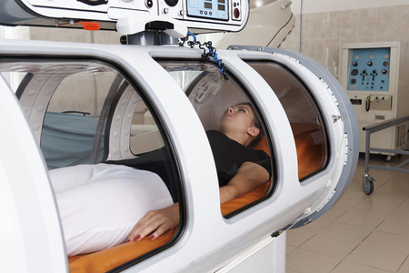 Girl patient lying in a hyperbaric chamber.