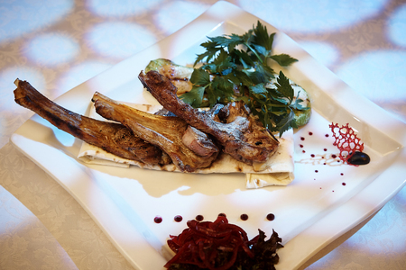 Baked lamb ribs with vegetables on a white plate.