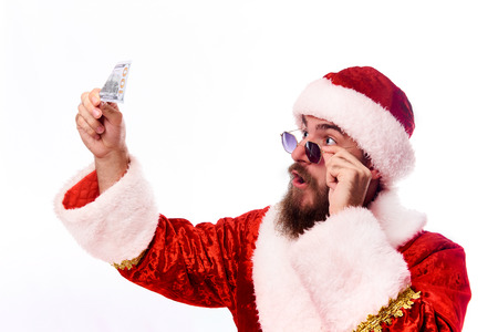 Emotional bearded young man in a Santa Claus suit and in glasses is looking at a hundred dollars in his hand.