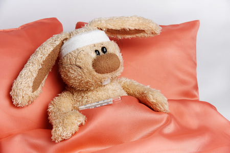 Toy unhealthy rabbit with a bandaged head and with a thermometer lies in bed.