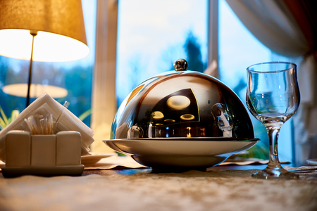 �¡loche with dish close-up on a serve table against the background of the window.Deep metal dishes with a lid for serving cooked food on the table.