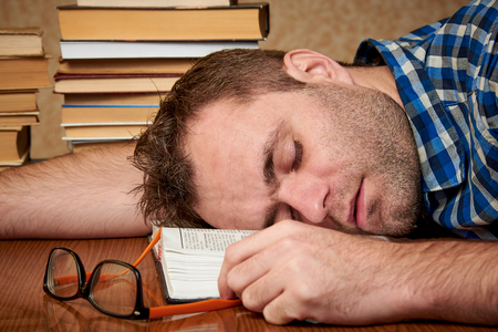 A tired and tortured disheveled student with glasses is sleeping at a table with stacks of books.