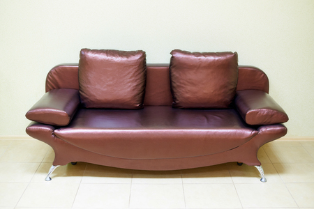 Leather sofa with pillows near the light wall. Stockfoto