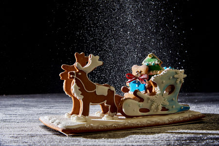 Christmas gingerbread sleigh with deers on a dark background with falling snow.