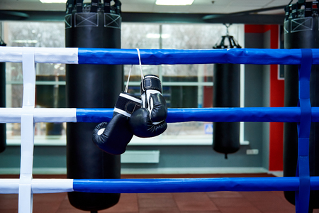 Boxing gloves in a boxing ring with bags in the gym.
