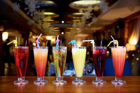 Row of different cocktails with straws on a blurred background.
