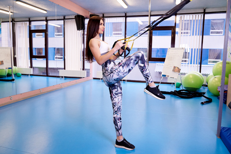 Young beautiful girl exercising with fitness straps in the gym.
