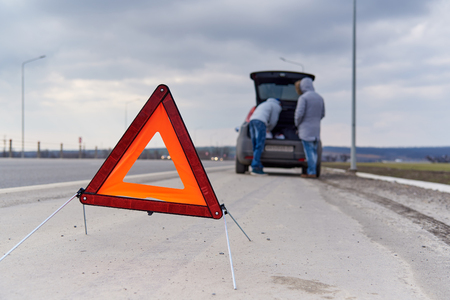 Warning sign on the road on a blurred background of people near the car. Reklamní fotografie