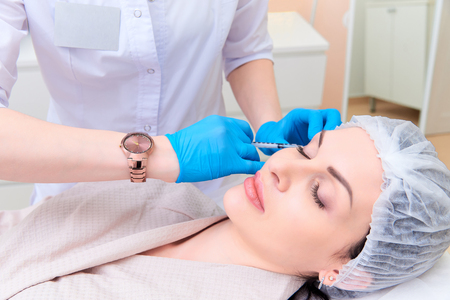 Beautiful young woman in aesthetic cosmetology clinic. Imagens