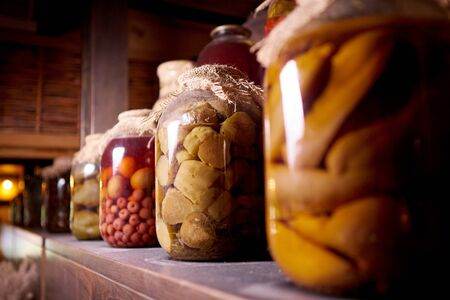 Preserved food on a wooden shelf in the dust.