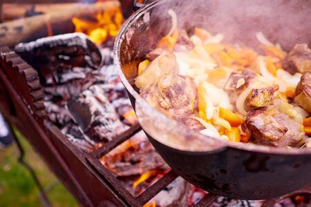 Cooking meat with vegetables on the fire.