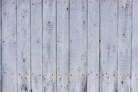 Background texture of the old wood covered with faded and cracked paint.