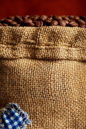 Burlap sack with coffee beans close-up. Stock fotó