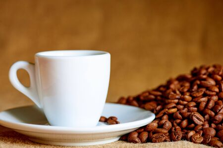 White cup and coffee beans on a blurred background. Stock fotó
