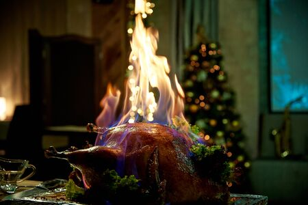 Burning baked turkey on a tray in a dimly lit room.