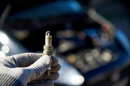 Spark plug for engine in male hand on the background of a car with an open hood.