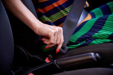 Young woman fastens a seat belt in car.