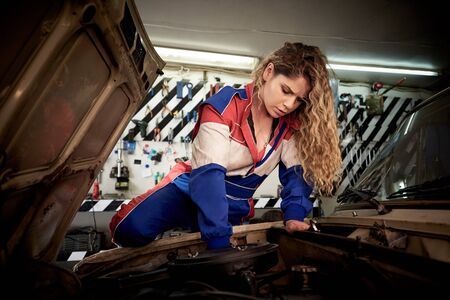 A young woman in overalls on a garage is repairing a auto. 免版税图像