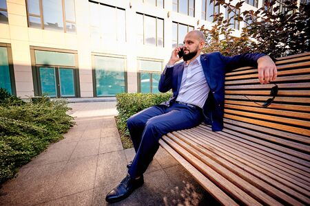 A successful young man is sitting on a bench near a business center.