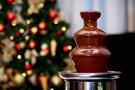 Hot chocolate fountain on the background of the Christmas tree.