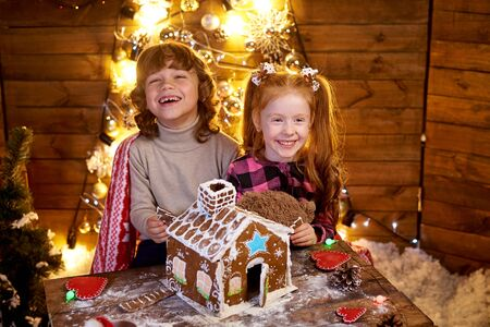 Happy redhead little girl at the table with christmas gingerbread. 免版税图像