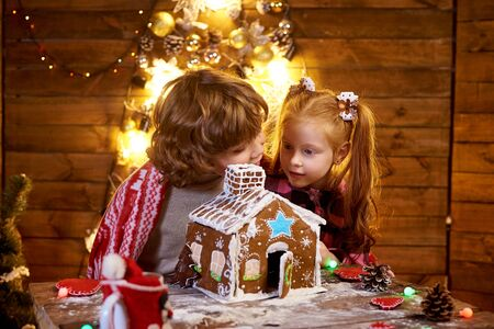 The little red haired girl looks on the christmas gingerbread with interest.