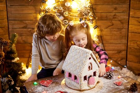Happy children with christmas gingerbread in a decorated room to the holiday. 免版税图像