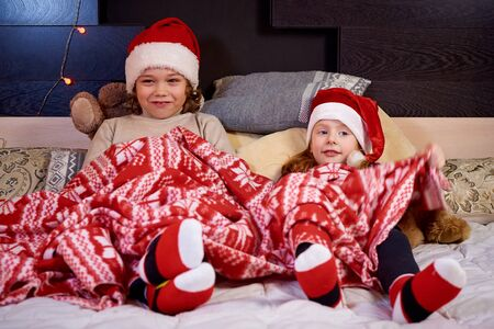 Happy kids on bed awaiting christmas. 免版税图像