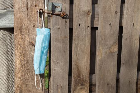 medical mask hanging on a hook an old wooden gate in Ukraine on the street during