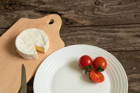 soft brie cheese and cherry tomatoes on a table