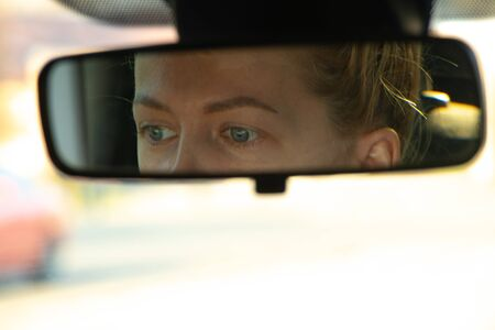 girl's eyes in the rearview mirror in the car while driving Imagens