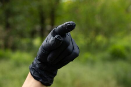 hand in medical gloves on a blurry background in the street