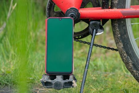 phone with a green screen stands on a bicycle on the street for a walk